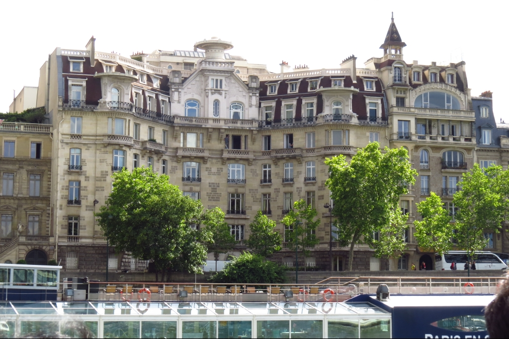 View from the boat, a Parisian building stands above the river behind several green trees. This building is about six stories high a neutral beige and has dozens of windows.