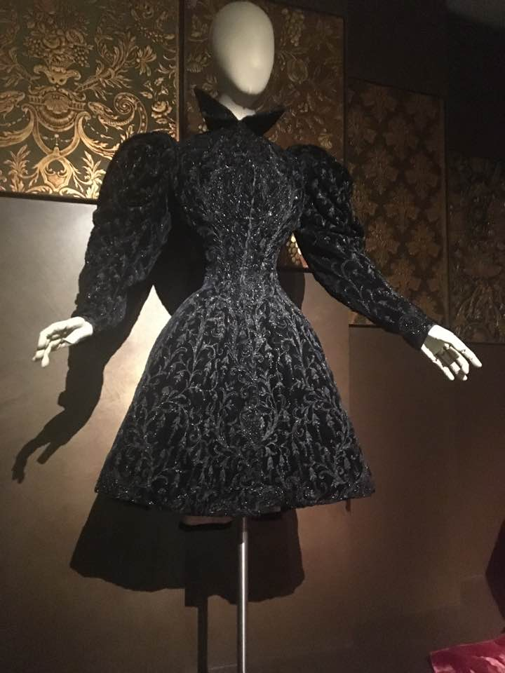 A white faceless mannequin stands in front of a chocolate brown wall wearing a short black and sparkly peplum dress - there is a high collar and long puffed sleeves.