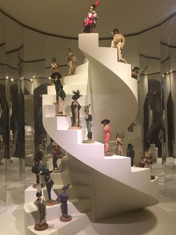 A spiral staircase to nowhere in the middle of the room, each step has a miniature mannequin in a different fashion deisgn