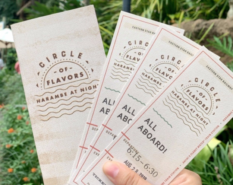 "Writer holds one booklet that says Circle of Flavors and three entry tickets that read ""All Aboard"""