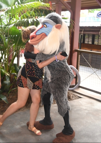 Writer is shown from the side in a black romper and sandals. Her face is hidden as she hugs Disney's Rafiki, a grey baboon.