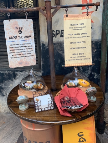 This is the display for the first station. There is a sign that lists each dish and a wooden table with napkins, silverware, and two display dishes under glass lids.