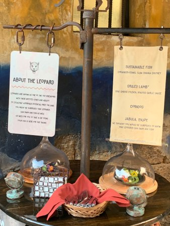 This is the display for the Leopard booth. There are two dishes displayed under glass covers, silverware, and napkins. There is also a sign that lists each dish.