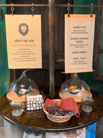 This is the display for the Lion station. There are two dishes displayed under glass covers. There is a sign listing each dish. There is also napkins and silverware.