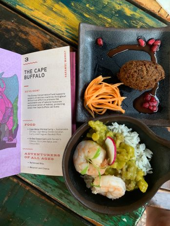 There are two dishes. One has a fried brown fritter with a few shredded carrots and surrounded by a purple pomegranate sauce and some pomegranate seeds. The second bowl has white rice with a thick bright green sauce, topped with two booked shrimp and a shred of radish.