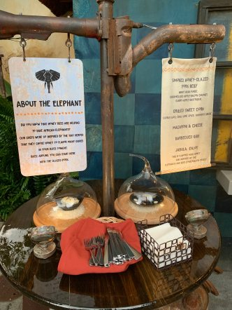 This is the set up front the elephant-themed station in front of the order window. It shows all three dishes under glass covers. There is a sign that lists each dish and some silverware and napkins.