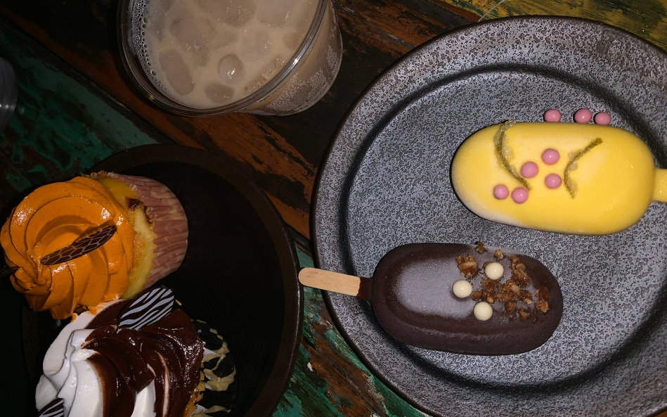 There are two plates. One has two cupcakes, one with orange frosting one with brown and white swirled frosting. The other plate has two frozen ice cream bars. One is dark chocolate dipped, the other in yellow-tinted white chocolate with pink candy pearls. And a beige alcoholic drink with ice.