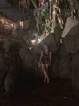 Writer stands in front of a mock Asian ruin of a dragon at Disney's Animal Kingdom Park. It is night. She wears a black romper and sandals and smiles at the camera.