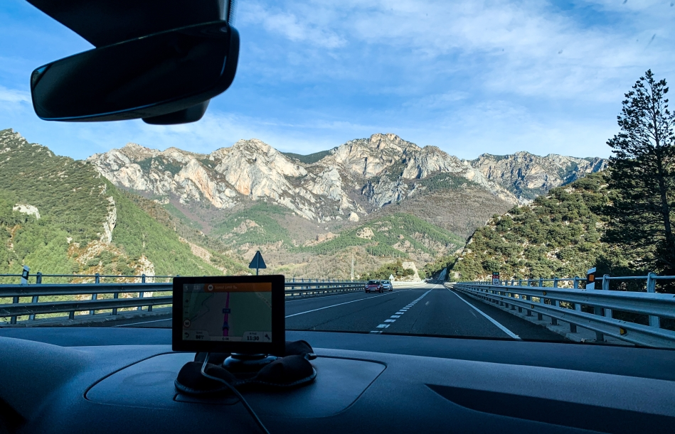 View from the front window of a car, GPS sits on the dashboard. Behind it a blue sky, scarcely clouded with a sedimentary mountain range. It has stripes of colors from green to grey to brown to beige.