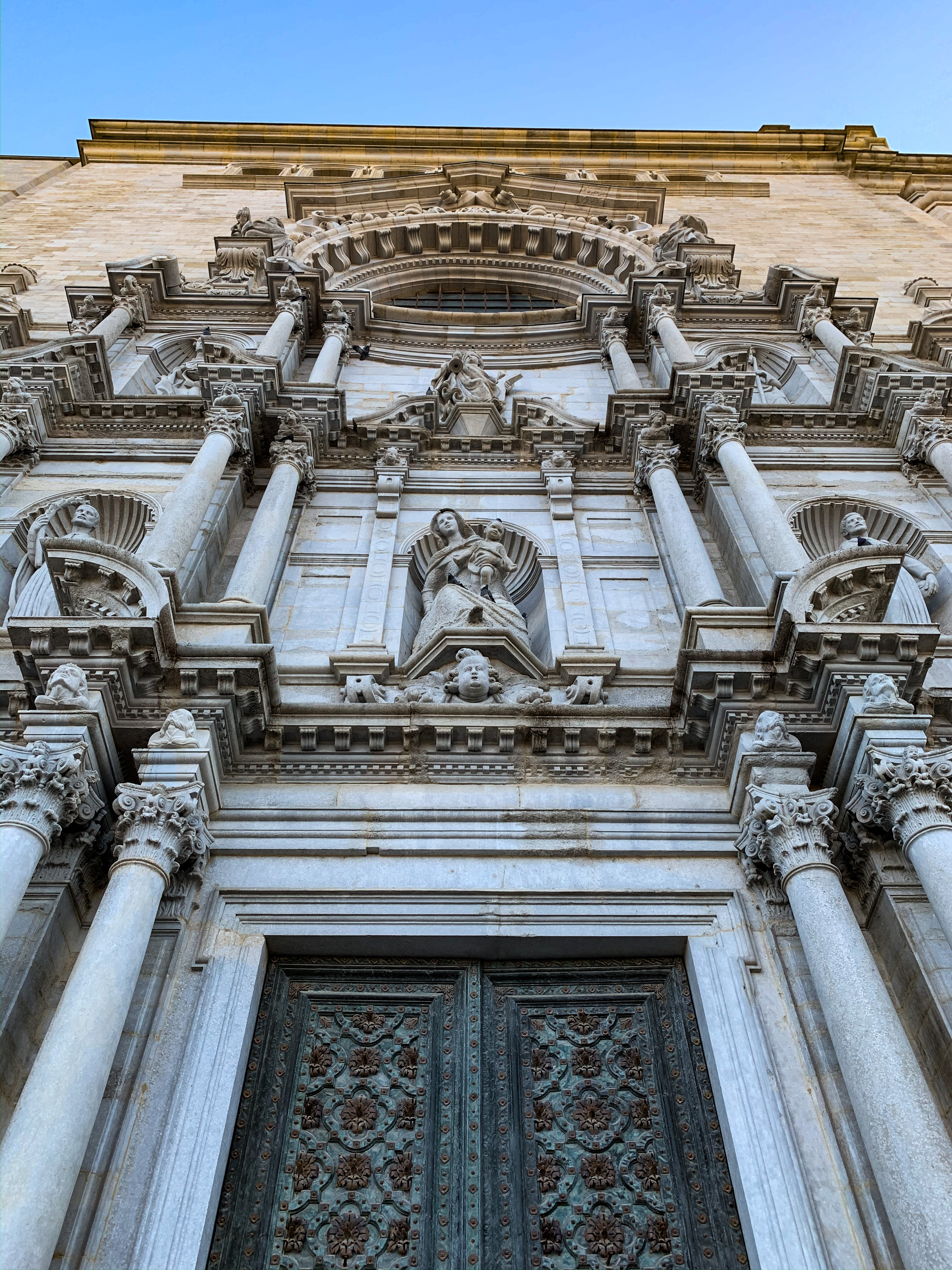 A close-up view of Girona Cathedral looking upwards. The building is tall with carvings of angels, saints, and other holy icons.