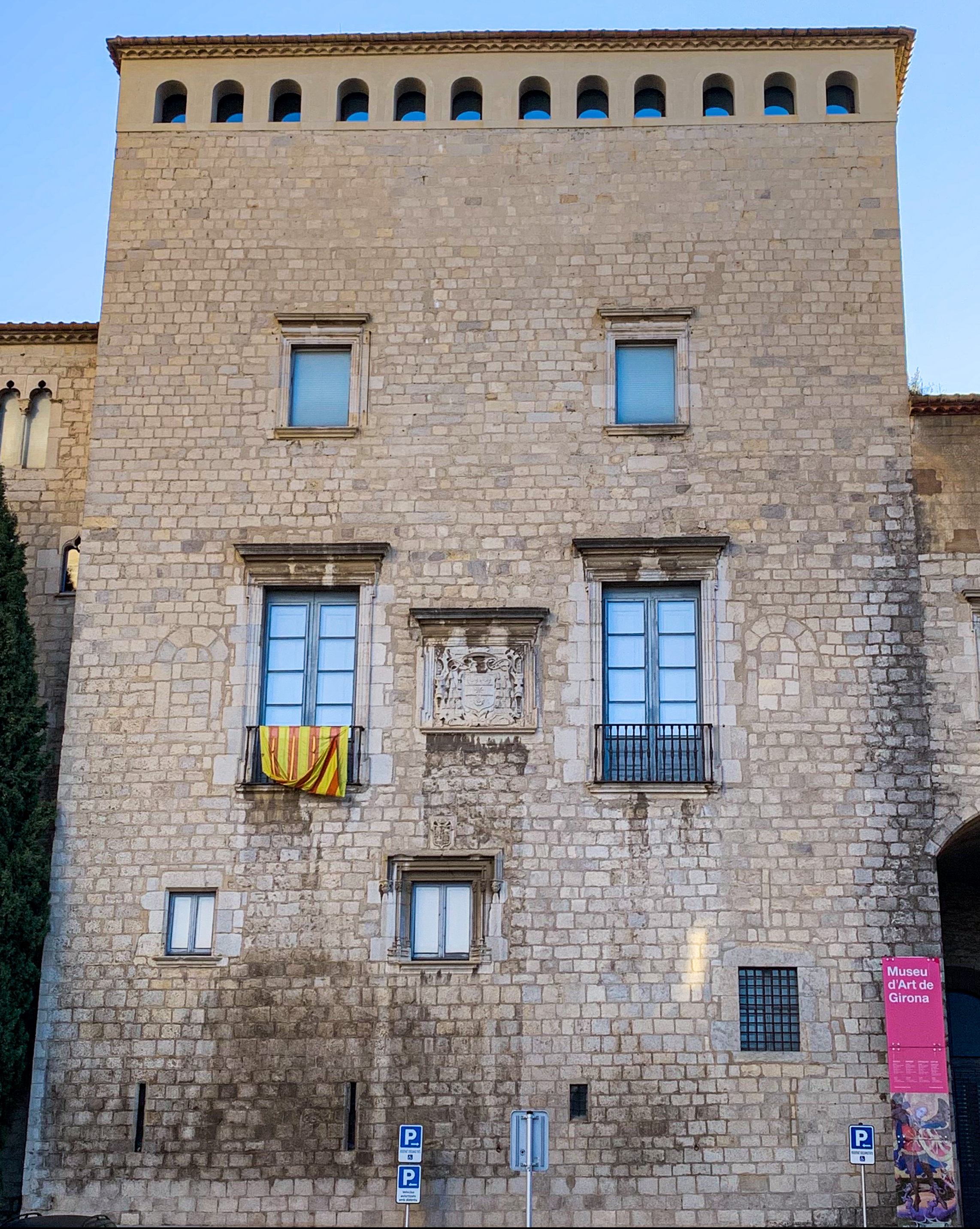 Front face of a beige stone building. TO the far right is a hot pink sign that says Museu d'Art de Girona. In the center of the building are two double pane windows. One has a yellow and red striped flag hanging off the balcony.