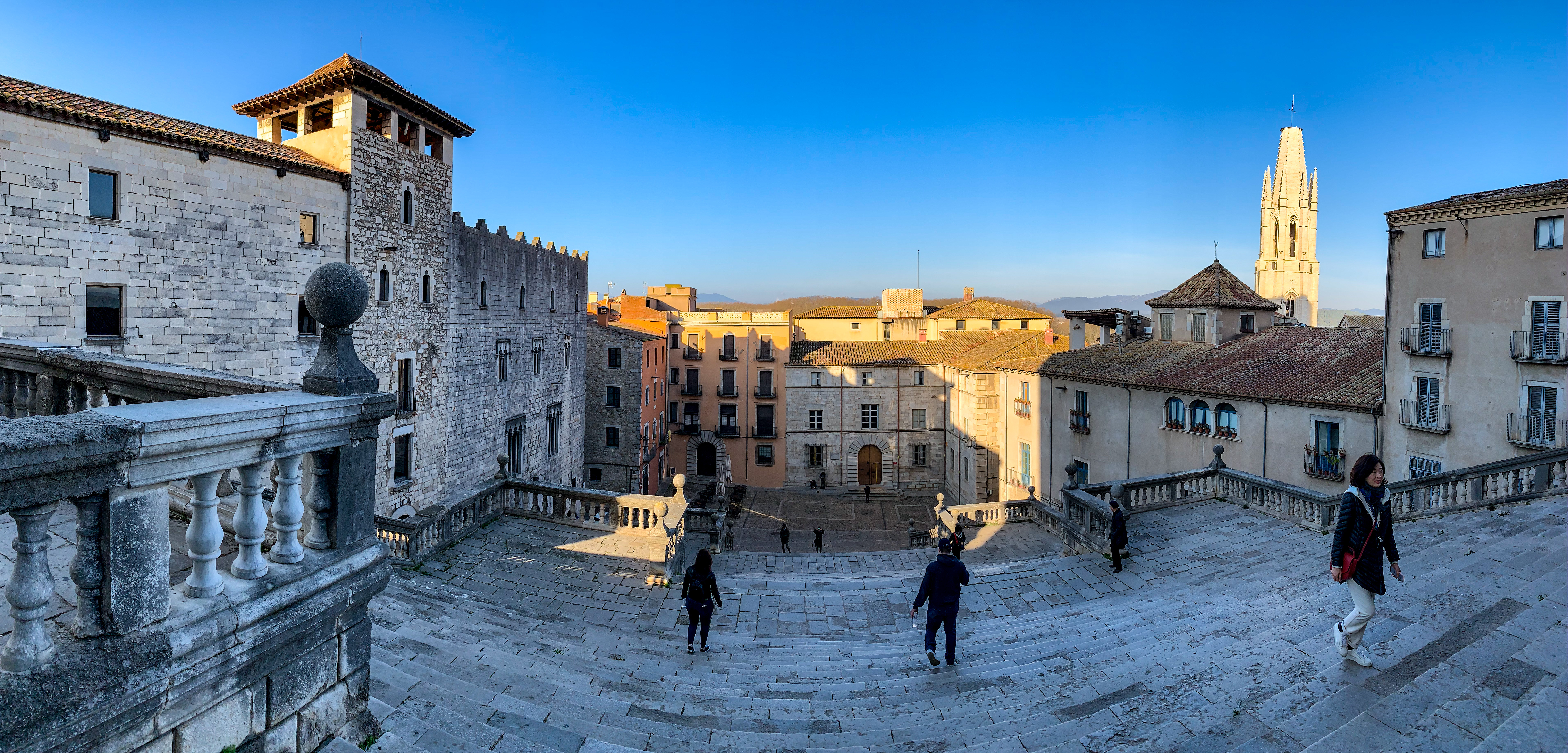View from in front of Girona Cathedral facing away and down the stairs. We see wide descending stone steps, a couple of people walking in different directions. Small Mediterranean attached houses stand at the bottom. The sun is shining slightly over them.