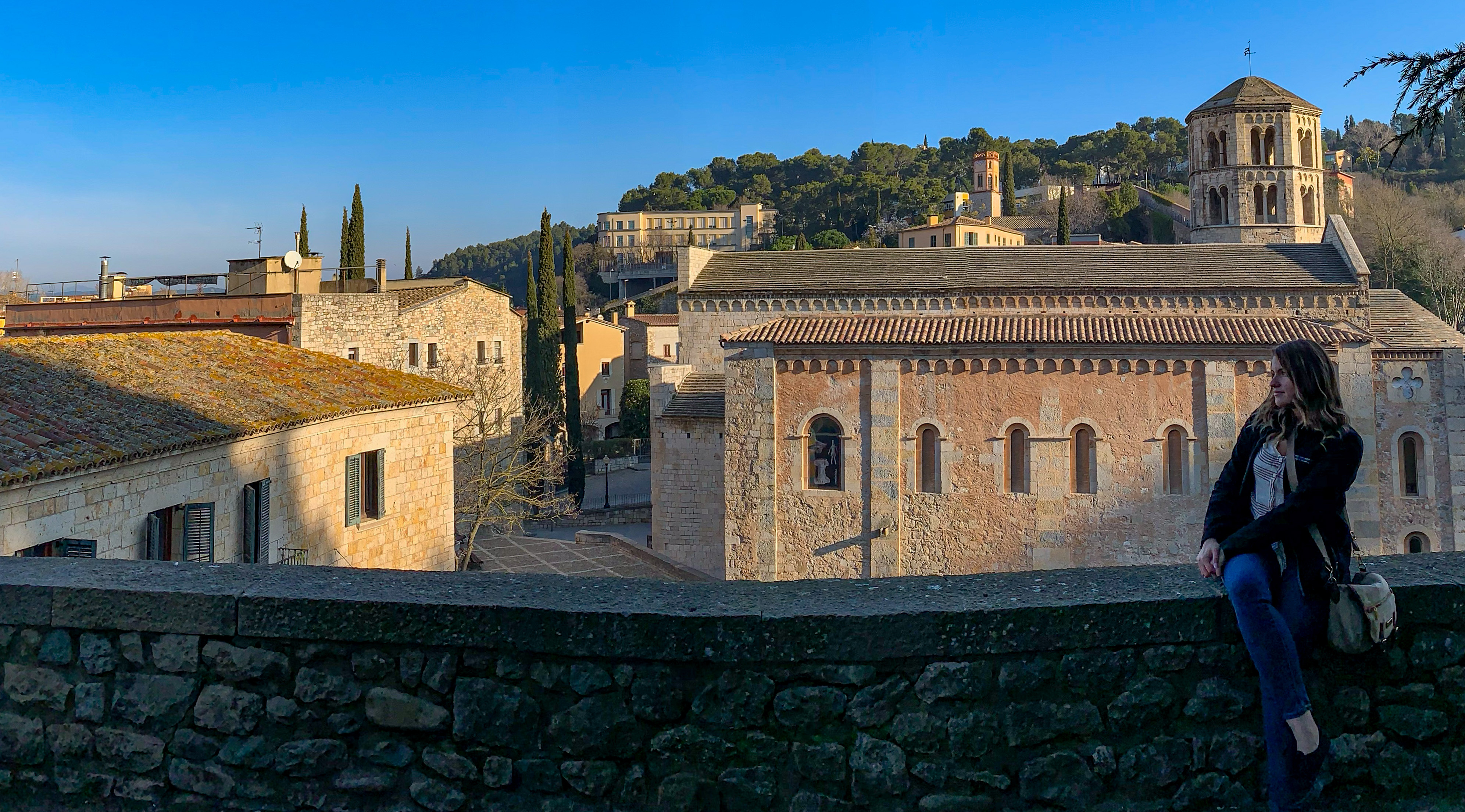 Writer sits on the right hand side of a short stone wall facing left with legs crossed. Behinds her are the roofs of a couple of Mediterranean buildings and a small tower to the right. Tall green trees stand behind the buildings.
