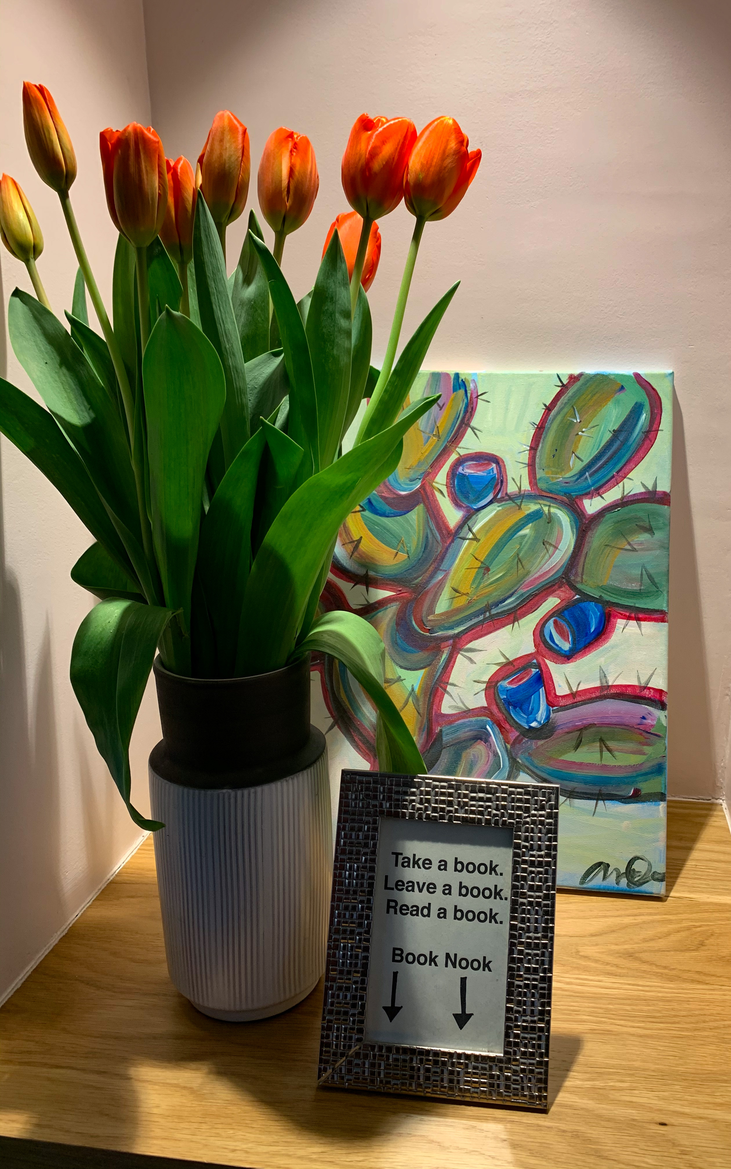 """To the left on a shelf, a white vase of orange and yellow hybrid tulips. In front of the flowers is a small framed sign that reads """"take a book, leave a book, read a book"""" with a down arrow gesturing to the book nook below."""