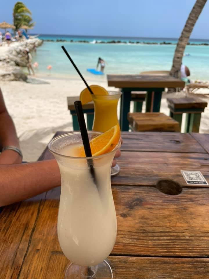 A wooden table with sand and light blue water behind it, on the table is a tall glass with a pina colada and orange wedge and in another a mango daiquiri