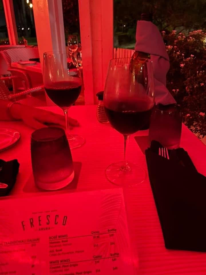 Red lighting, on the table are two glasses of red wine and a menu that says Fresco on top