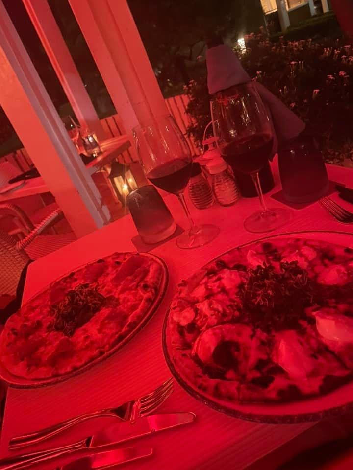 Red lighting, looking down at a table with silverware, two glasses of red wine and two small pizzas. one with prosciutto and one with burrata and balsamic reduction