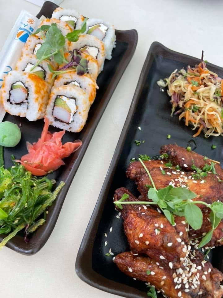 Two black rectangular plates of food, the first has green seaweed salad, orange ginger, a ball of wasabi and a sushi roll of ten pieces of sushi topped with orange caviar. The second has several chicken wings covered in sesame seeds and a multicolor asian slaw