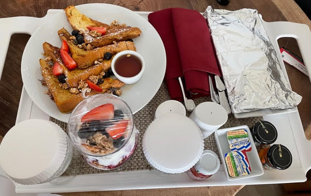 Looking down on a room service tray, from left to right is a white plate of four triangular slices of french toast topped with blueberries and strawberries, a wine glass with a yogurt, fruit, granola parfait, a covered plate of bacon and small butters and jams