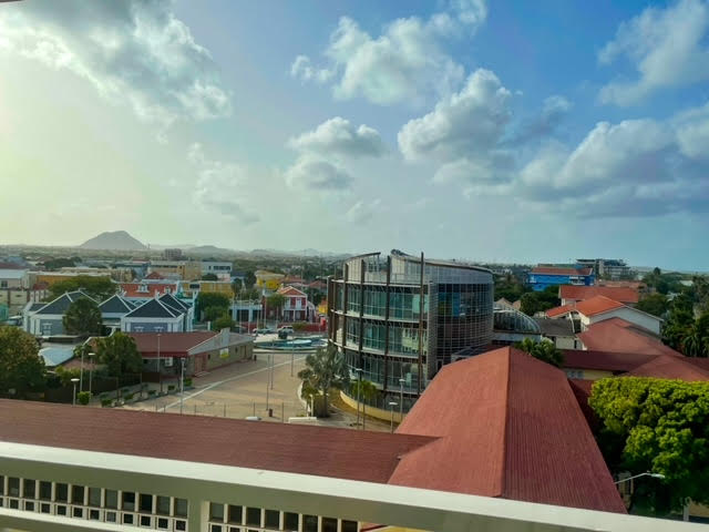 Balcony view from room, there are the several brightly colored houses below and one modern building in the enter. The sky is light blue, almost sunset with many clouds