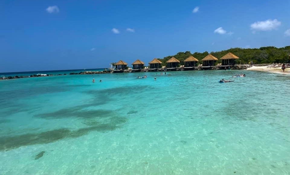 see-through light blue water, a few people float on floats in the distance, in the back a row of seven private cabanas