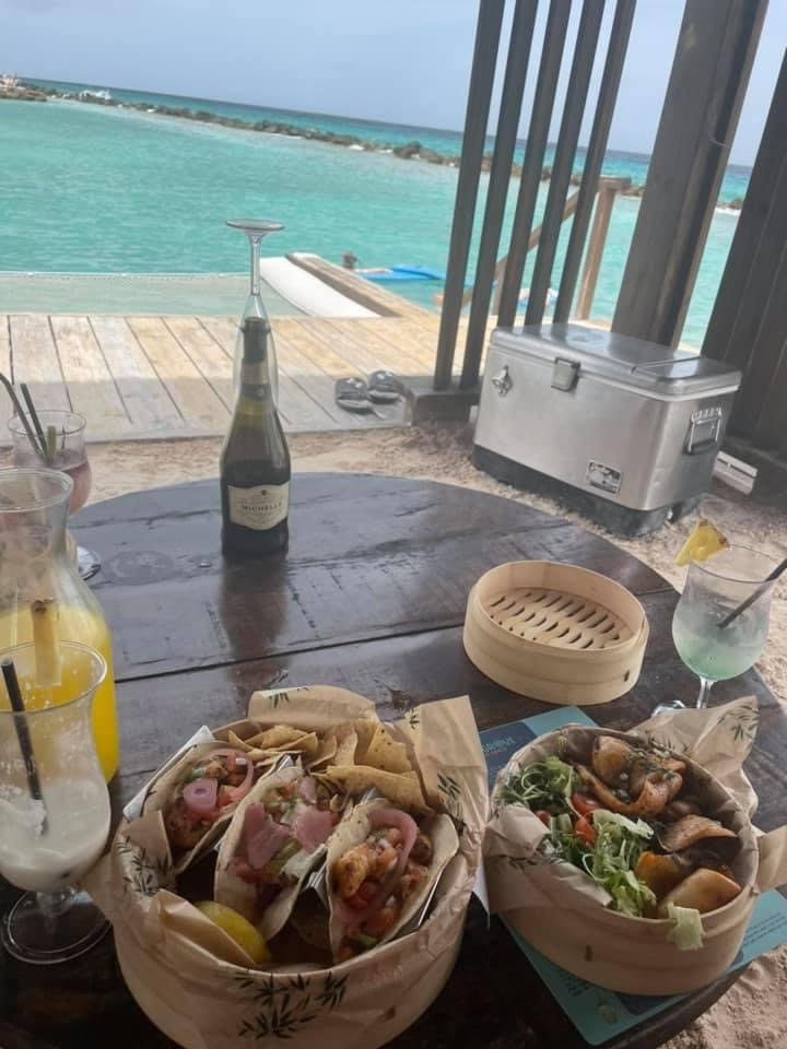View from inside a cabana, a hammock hangs over the light blue ocean, on the wooden table is a carafe of orange juice and bottle of champagne as well as a finished pina colada and two wooden bowls. One with three shrimp tacos and chips and one with salad and grilled octopus
