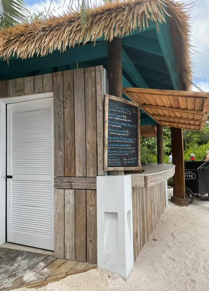 A beach hut on the sand, on the hut is a menu with several seafood items for order