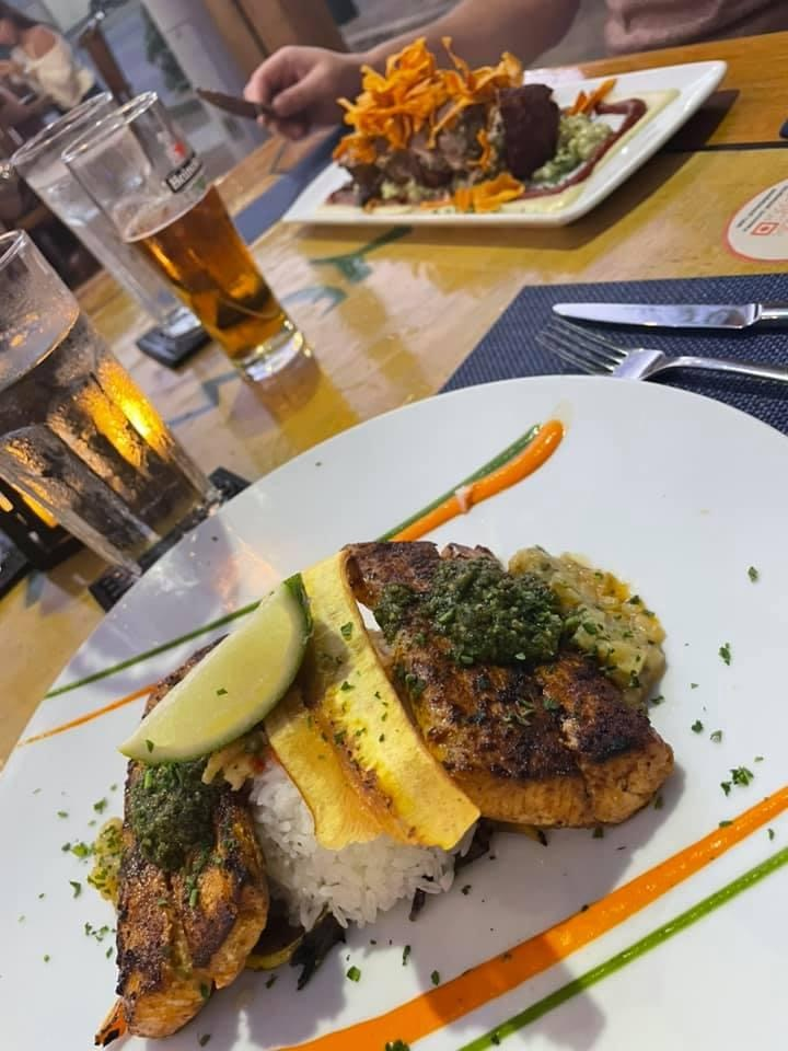 A white plate with two lines of an orange and green liquid, on top is white rice surrounded by two pieces of mahi mahi fish and topped with a plantain chip and a wedge of lime. There is a glass of water and glass of beer in the background