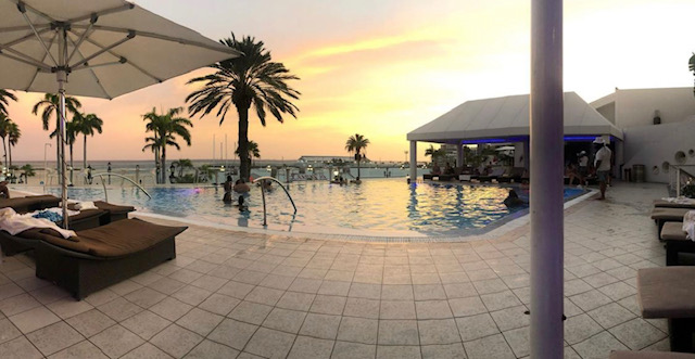 Sunset, the view from outside of the infinity pool. There's several people in the pool and a lounge chair with am umbrella to the left