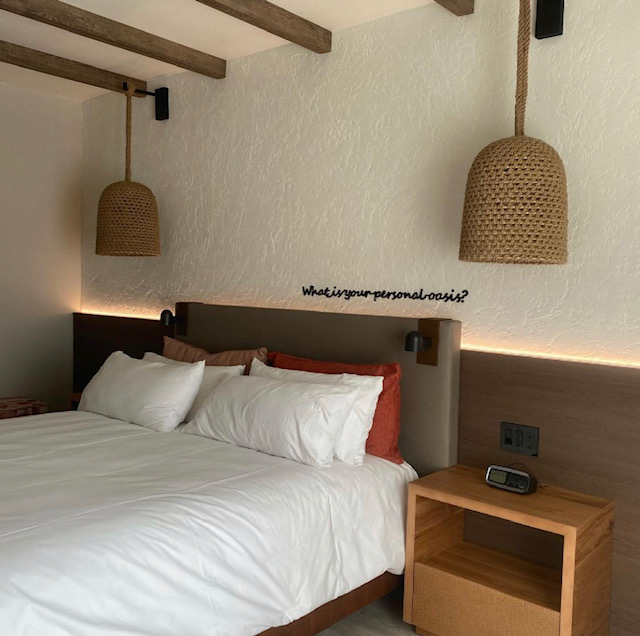 """Facing a white sheeted king size bed, to the right is a wooden nightstand with an alarm clock. Above the bed are two hanging lamps and wording that reads """"what is your personal oasis?"""""""