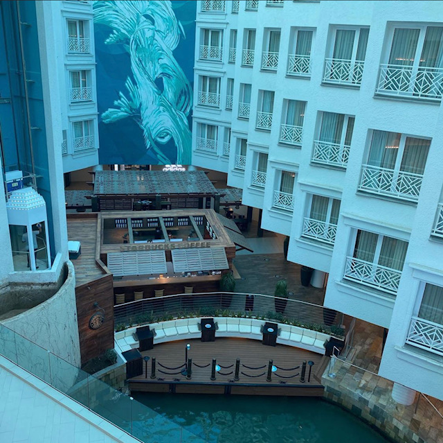 Looking down from the sixth floor into the resort atrium, we can see several windows into other rooms, and the lobby pick-up area from the private island boat