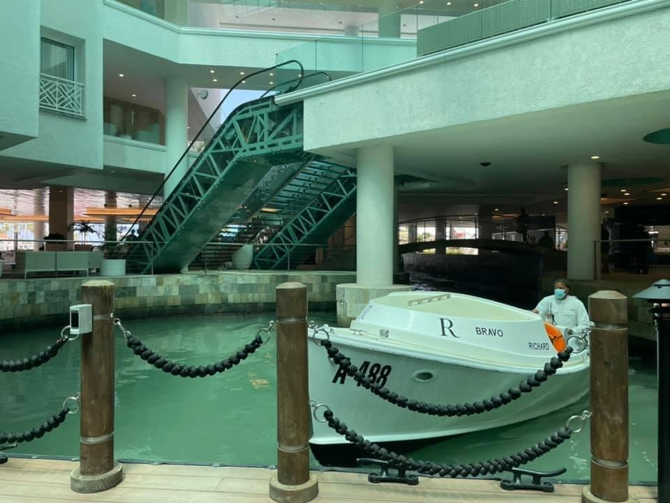 View from the dock pick-up inside the lobby, a white boat is driving up to the dock with a driver with a face mask on