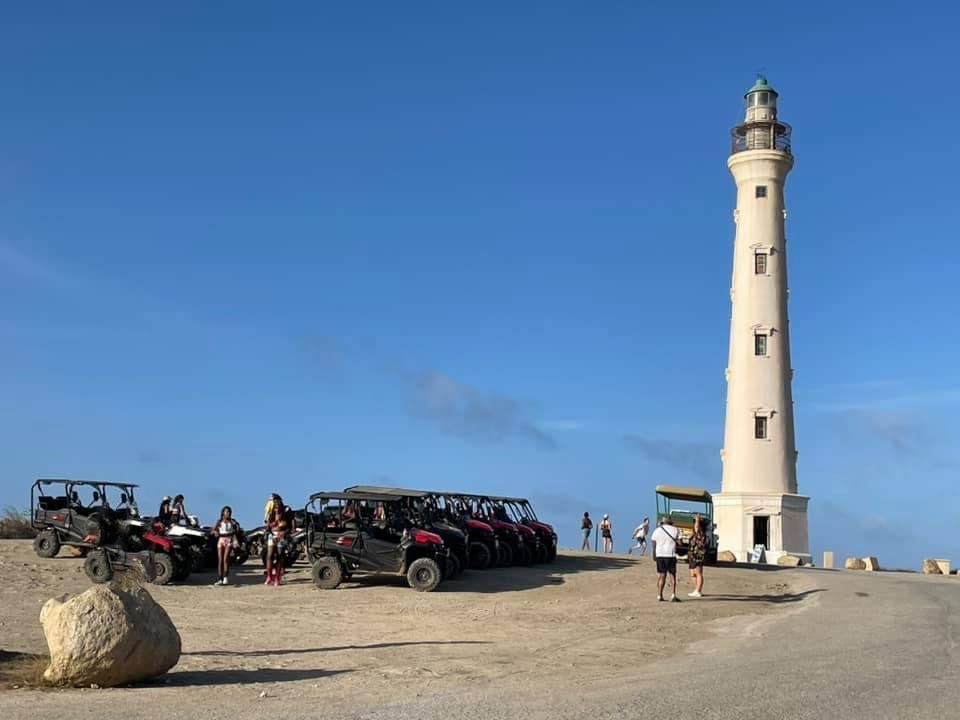 To the left are several parked ATVs and UTVs, to the right is the california lighthouse. The sky is cloudless and blue