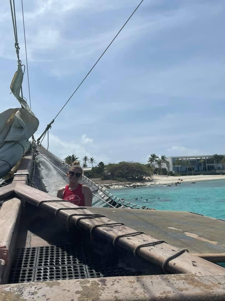 View of writer in red tank top and black sunglasses sitting near sale in a hammock at the tip of the ship