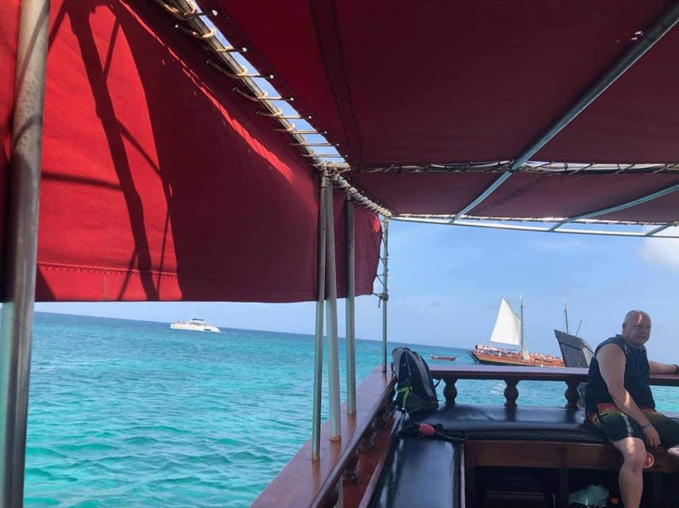 View from inside pirate ship facing out back. There is a red covering above us and to the water is clear blue. Further out is another pirate ship